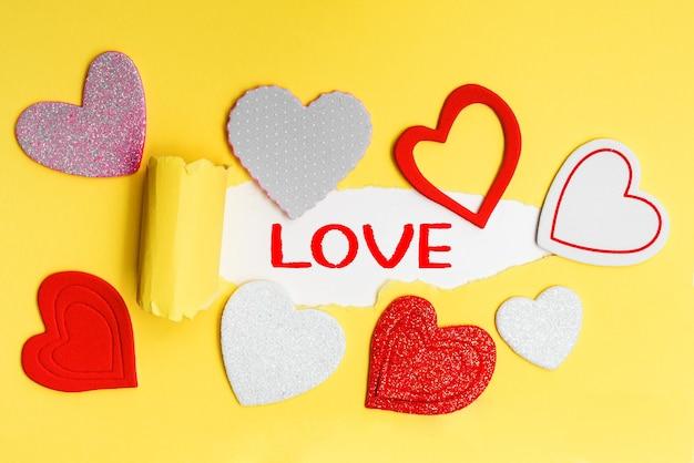 Englischer text liebe auf einem zerrissenen stück gelbem papier mit romantischen herzen. Premium Fotos