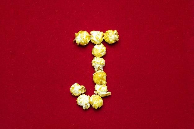 Englisches alphabet vom kinopopcornhintergrund, buchstabe j