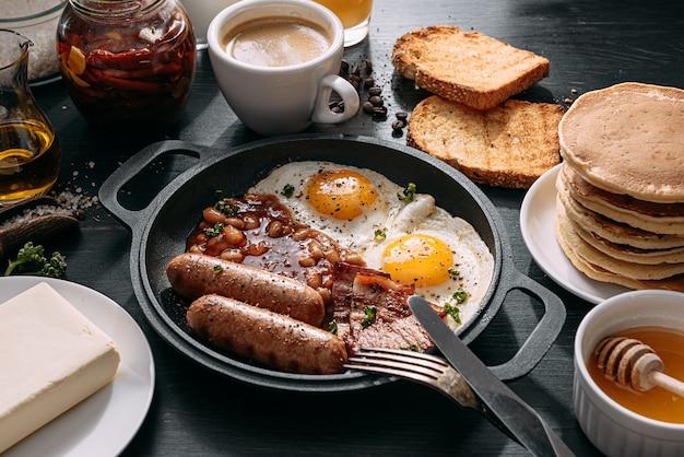 Englisches frühstück auf einem dunklen tisch spiegeleier mit speckbohnen und wurst