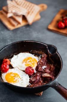 Englisches frühstück des spiegeleis, der tomaten, des speckes und des toasts auf grau