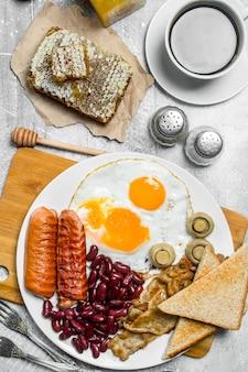 Englisches frühstück. eine vielzahl von snacks mit aromatischem kaffee. auf einer rustikalen oberfläche.