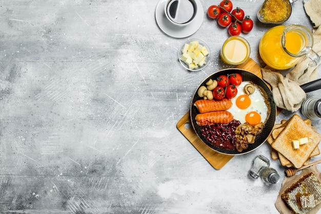 Englisches frühstück. eine vielzahl von snacks mit aromatischem kaffee auf rustikalem tisch.
