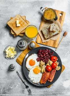 Englisches frühstück. eine vielzahl von snacks mit orangensaft. auf einer rustikalen oberfläche.