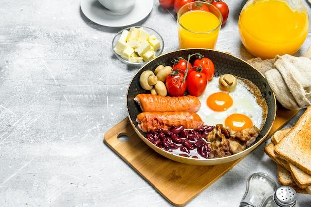 Englisches frühstück. eine vielzahl von snacks mit orangensaft auf rustikalem tisch.