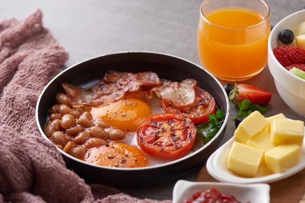 Englisches frühstück in der pfanne mit spiegeleiern, speck, bohnen, gegrillten tomaten.