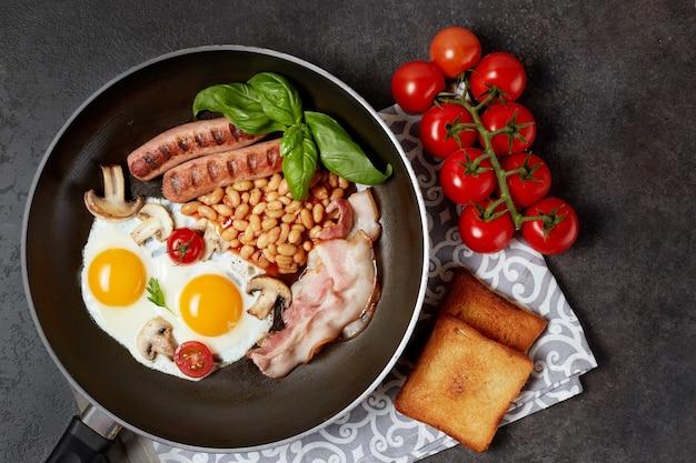 Englisches frühstück in der pfanne mit spiegeleiern, würstchen, bohnen, tomaten, pilzen, speck und toast auf holztisch. speicherplatz kopieren. draufsicht