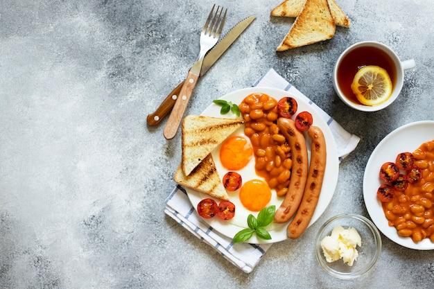 Englisches frühstück mit bratwürsten, bohnen, pilzen, spiegeleiern, gegrillten kirschtomaten. serviert mit einer tasse tee mit zitrone, toastbrot und butter. grauer hintergrund, draufsicht, copyspace