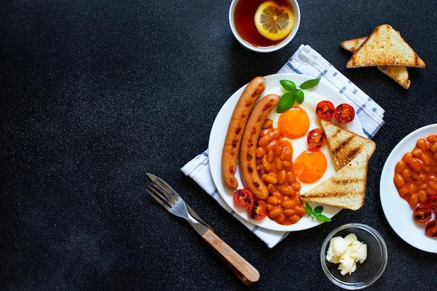 Englisches frühstück mit bratwürsten, bohnen, pilzen, spiegeleiern, gegrillten kirschtomaten. serviert mit einer tasse tee mit zitrone, toastbrot und butter. schwarzer hintergrund, draufsicht, copyspace