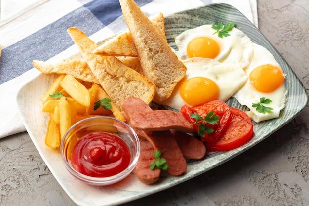 Englisches frühstück mit eierwürstchen, french toast und kartoffelecken auf grauem tisch gray