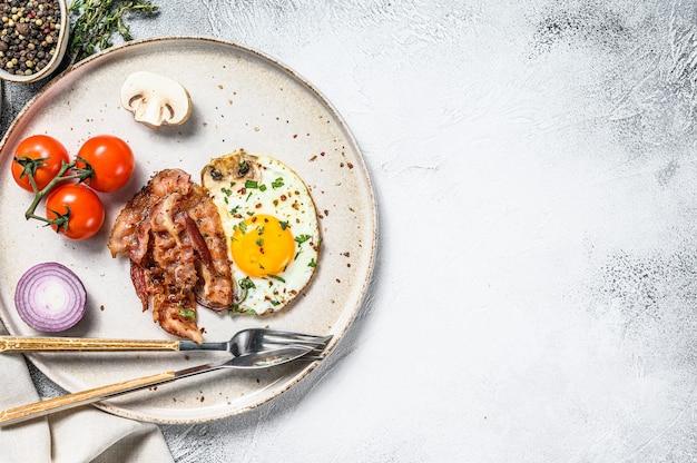 Englisches frühstück mit spiegelei, speck und gemüse