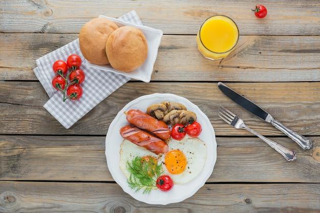Englisches frühstück mit spiegeleiern, würstchen, pilzen, gegrillten tomaten und frischem orangensaft auf rustikalem holztisch.