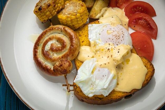 Englisches frühstück mit toast, pochiertem ei, sauce und wurst auf einem holztisch