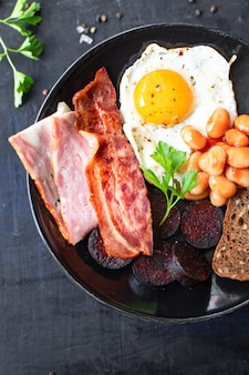 Englisches frühstück spiegelei blutwurst blutwurst müsli brot bohnen rührei auf dem tisch