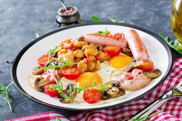 Englisches frühstück - spiegelei, bohnen, tomaten, pilze, speck und wurst. leckeres essen.