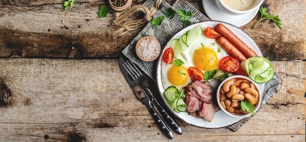 Englisches frühstück. spiegelei, bohnen, tomaten, speck und kaffee.