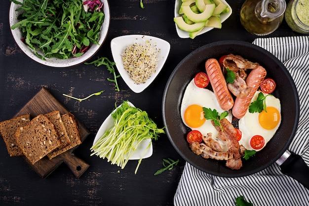 Englisches frühstück - spiegelei, tomaten, wurst und speck.