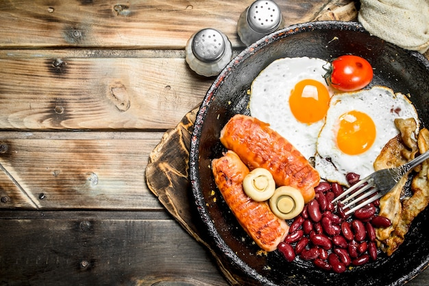 Englisches frühstück. spiegeleier mit tomaten, würstchen und bohnen auf rustikalem tisch.