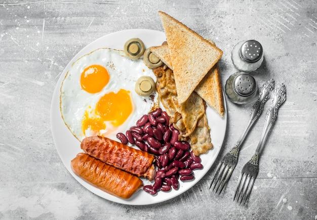 Englisches frühstück. spiegeleier mit würstchen, speck und bohnen. auf einer rustikalen oberfläche.