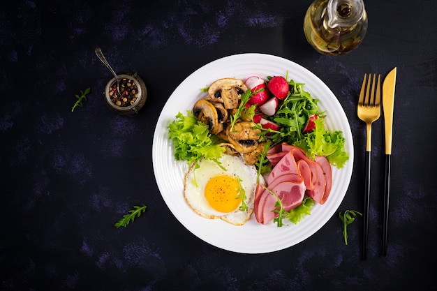 Englisches frühstück - spiegeleier, schinken, gebratene pilze, radieschen und rucola