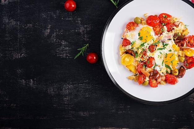 Englisches frühstück - spiegeleier, schinken, tomaten und rucola. amerikanisches essen. draufsicht, overhead, speicherplatz