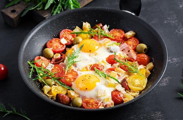 Englisches frühstück - spiegeleier, schinken, tomaten und rucola. amerikanisches essen.