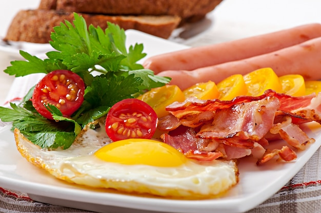 Englisches frühstück - spiegeleier, speck, würstchen und geröstetes roggenbrot