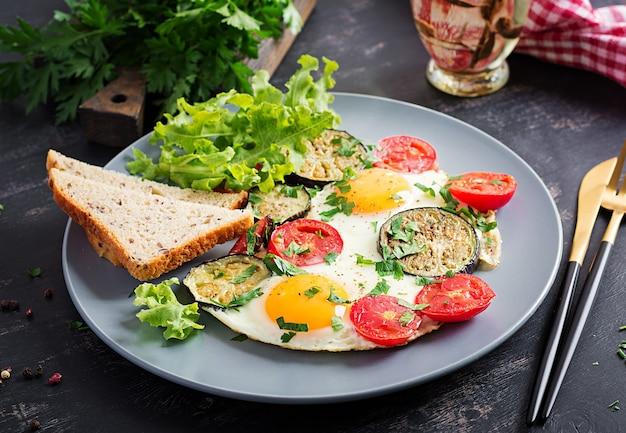 Englisches frühstück - spiegeleier, tomaten und auberginen. amerikanisches essen.
