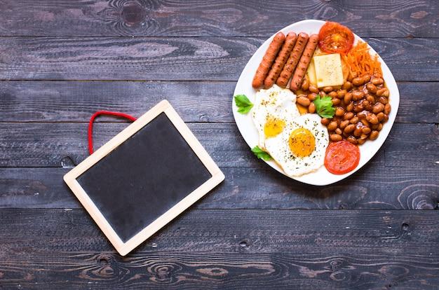 Englisches frühstück. spiegeleier, würstchen, bohnen, toastbrot, tomaten, käse,