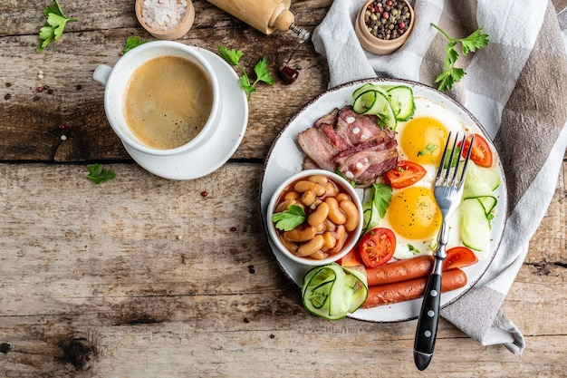 Englisches frühstück. spiegeleier, würstchen, speck, bohnen, auf holztisch.