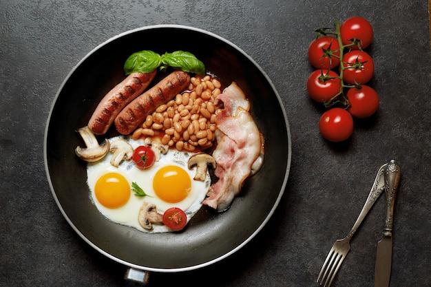 Englisches frühstück. spiegeleier, würstchen, speck, bohnen, toast, tomaten auf steintisch. draufsicht mit kopierraum