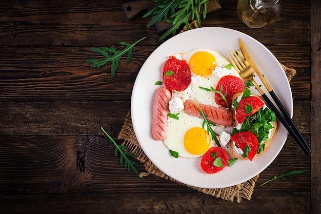 Englisches frühstück - spiegeleier, würstchen, tomaten und feta-käse. amerikanisches essen. draufsicht, overhead, speicherplatz