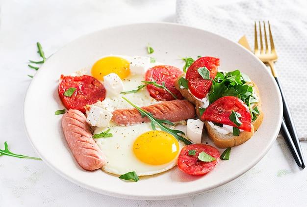 Englisches frühstück - spiegeleier, würstchen, tomaten und feta-käse. amerikanisches essen.