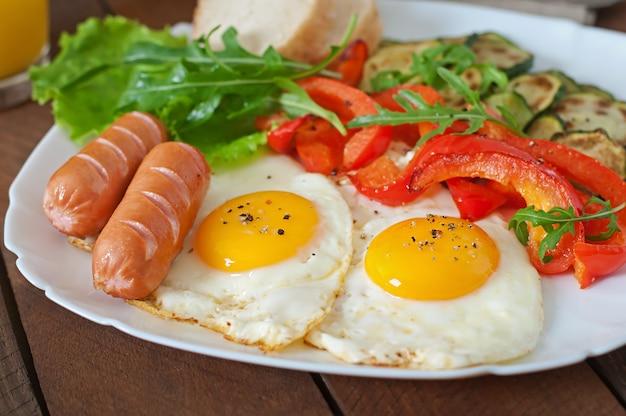 Englisches frühstück - spiegeleier, würstchen, zucchini und paprika