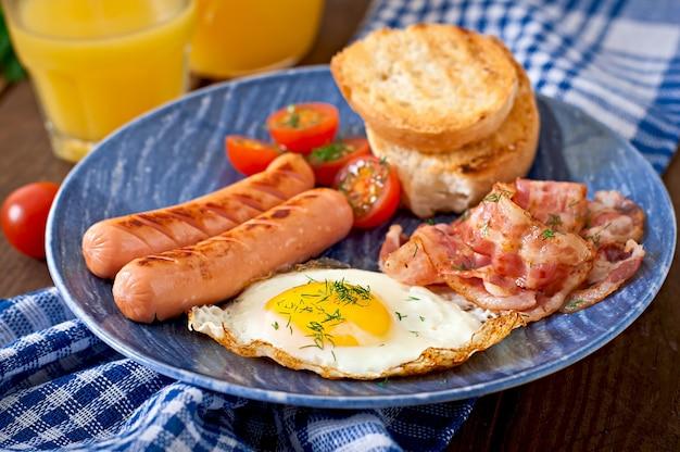 Englisches frühstück - toast, ei, speck und gemüse im rustikalen stil auf holztisch