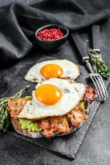 Englisches frühstück, toast mit speck, avocado und ei auf einem schneidebrett auf schwarz. draufsicht