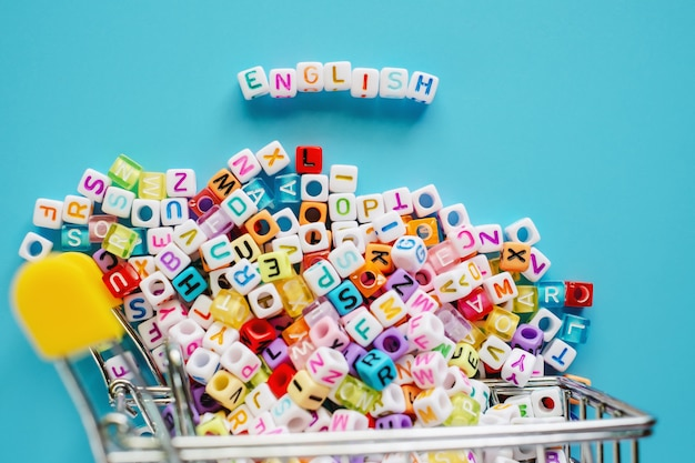 Englisches wort mit miniwarenkorb oder laufkatze voll von buchstabeperlen auf blauem hintergrund