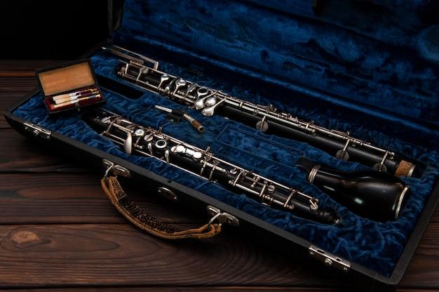 Englischhorn oder oboe in einem fall mit schilf zum spielen auf einer holzoberfläche