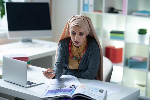 Englischlehrer. junge englischlehrerin, die hijab trägt, fühlt sich an der unterrichtsvorbereitung beteiligt