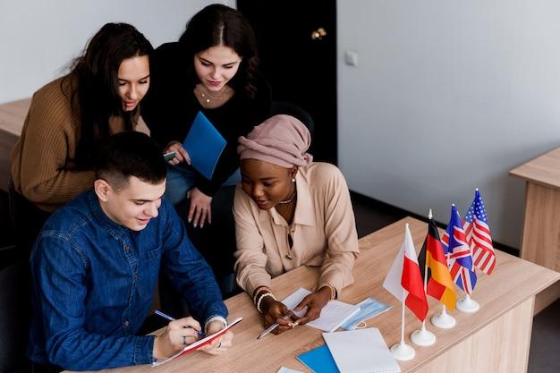 Englischunterricht mit studenten aus verschiedenen ländern: polen, deutschland, usa. zusammenarbeit. arbeiten in multiethnischen studenten. lehrer lernen gemeinsam fremdsprachen im unterricht. studieren mit laptop. Premium Fotos