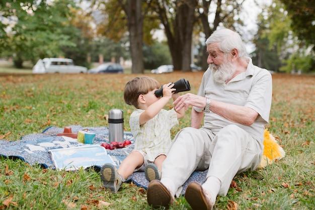 Enkel, der großvater mit binokularem betrachtet