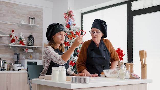 Enkel mit schürze bei der zubereitung köstlicher hausgemachter lebkuchen
