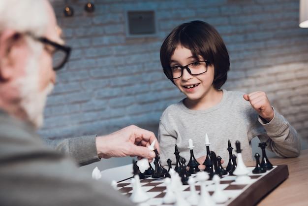 Enkel und großvater, die zusammen schach spielen