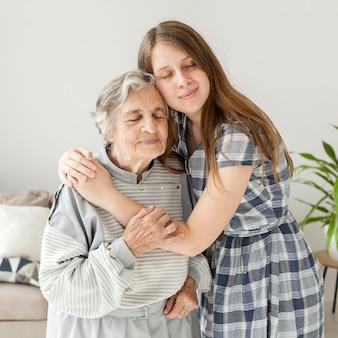Enkelin, die großmutter mit liebe umarmt