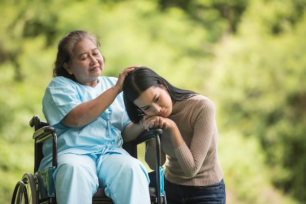Enkelin, die mit ihrer großmutter sitzt auf rollstuhl, nettes konzept, glückliche familie spricht