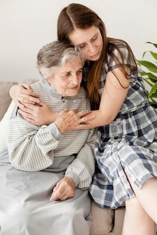 Enkelin, die oma zu hause umarmt