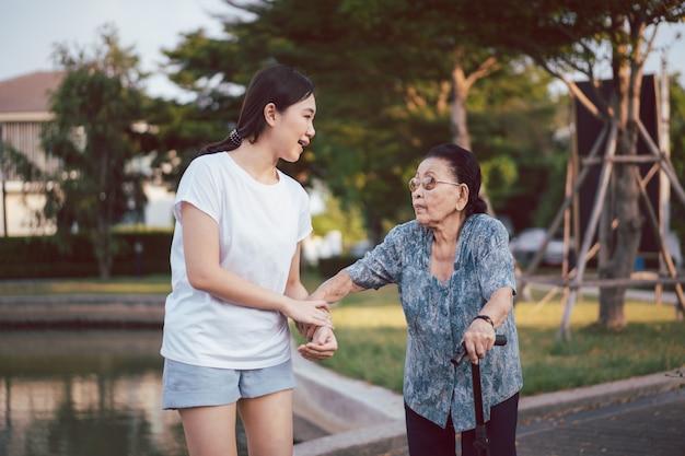 Enkelin hilft ihrer großmutter, deren alter fast 90 jahre alt ist, beim gehen