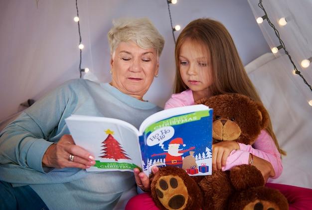 Enkelin mit großmutter, die ein bilderbuch beobachtet