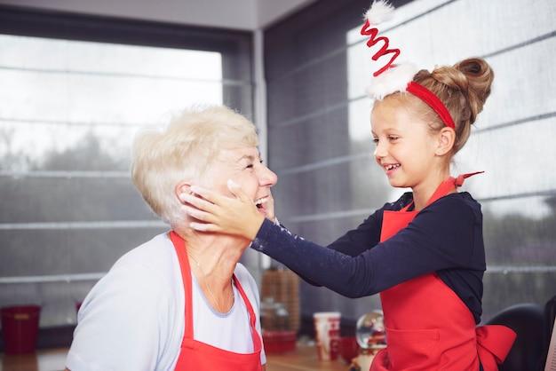 Enkelin reibt mehl auf das gesicht der großmutter