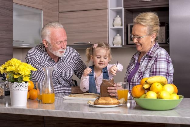 Enkelin spielt mit ihren großeltern in der küche