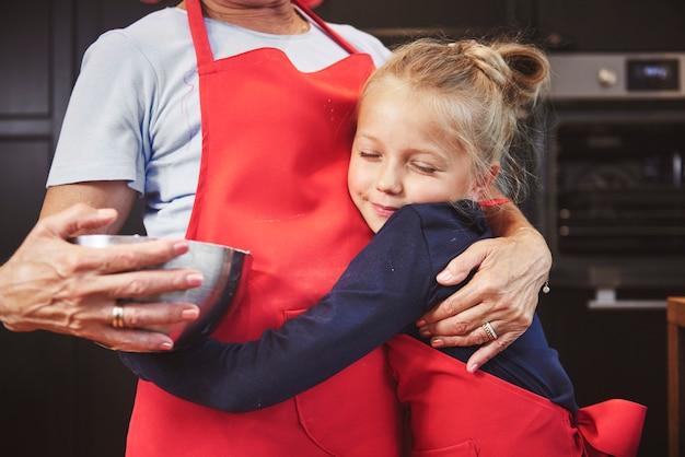 Enkelin umarmt ihre großmutter in der küche